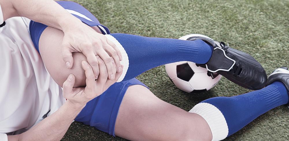 Close das mãos de um jogador de futebol com estado de dor em seus joelhos