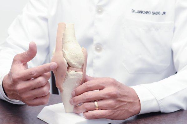 Close das mãos do médico ortopedista especialista em joelho em uma prótese do joelho