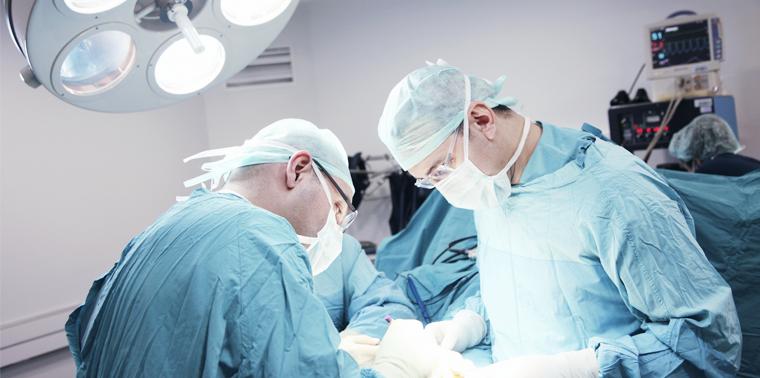Sala de cirurgia com dois médicos realizando cirurgia de artroscopia do joelho